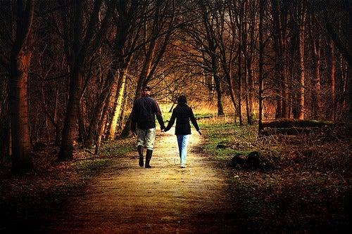 par holder hender i skogen