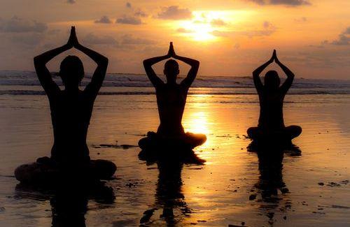 Tre mennesker gjør yoga på en strand