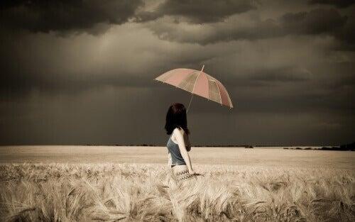 kvinne paraply stormfull åker