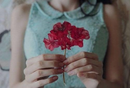 kvinne-med-rod-blomst