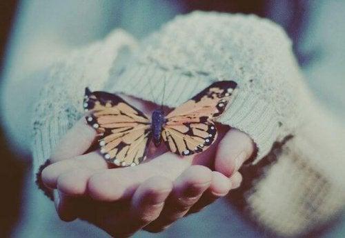kvinne-med-sommerfugl-i-hånden