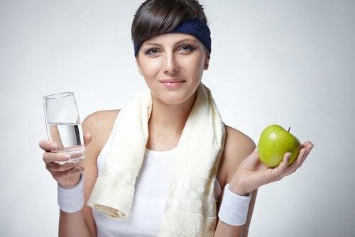 Kvinne holder et glass vann og et eple