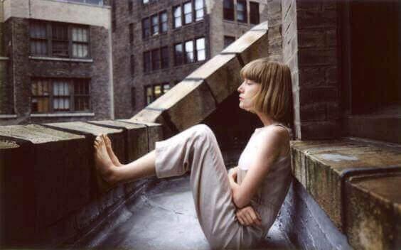 Kvinne  sitter på tak-terrasse