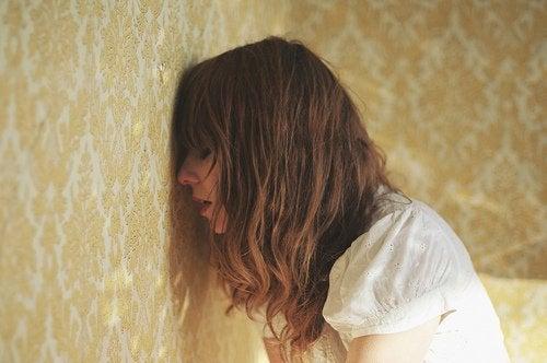 Kvinne stanger hodet mot veggen
