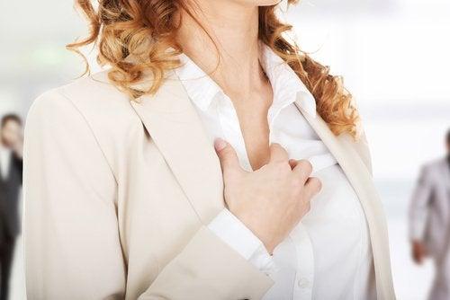 kvinne tar seg til brystet