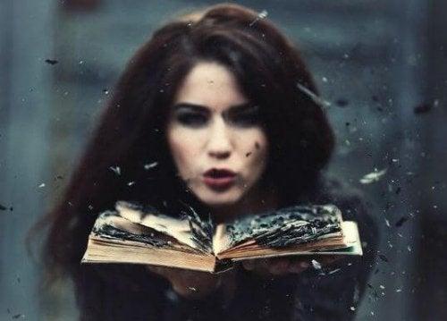 Kvinne blåser bort brent papir