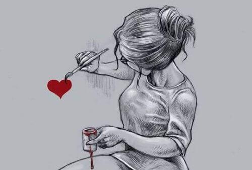 Kvinne tegner hjerte på veggen