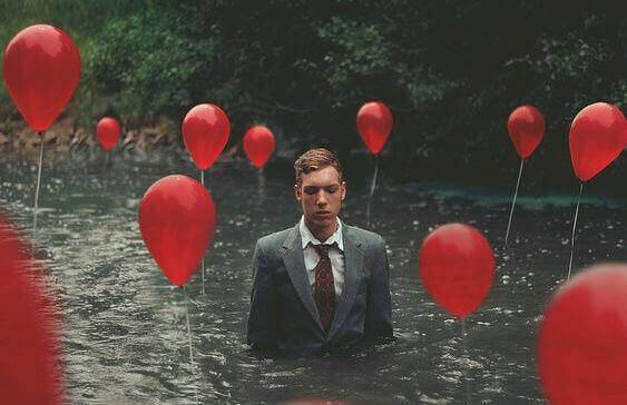 Mann står i dypt vann med ballonger