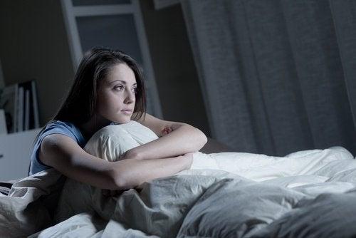 Deprimert kvinne sitter i sengen