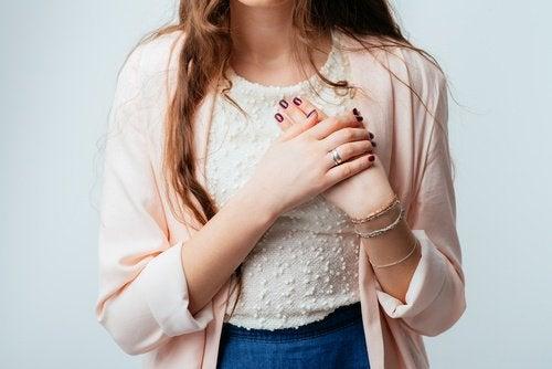 kvinne med hånden på brystet
