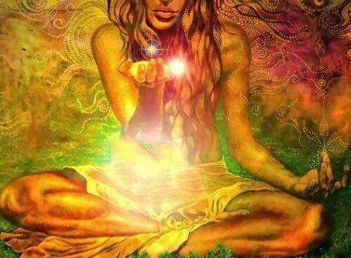 Kvinne mediterer og holder et lys