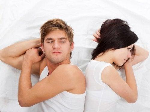 Mann og kvinne rygg mot rygg i sengen