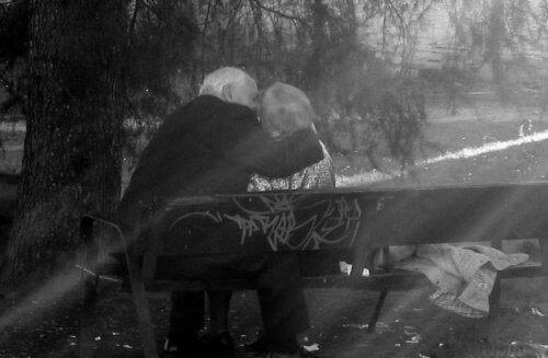 Eldre par kysser på en benk