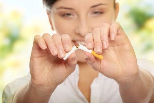 kvinne brekker en sigarett i to