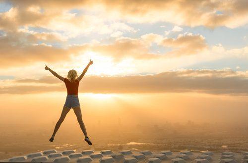 kvinne hopper i soloppgang