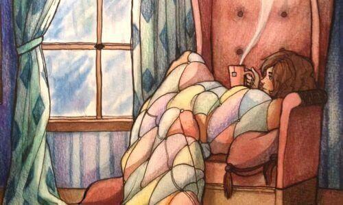 Jente med pledd drikker te