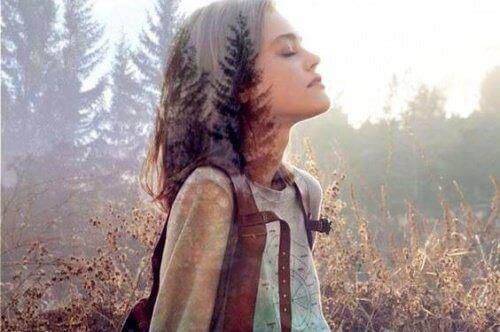 kvinne lytter i skogen