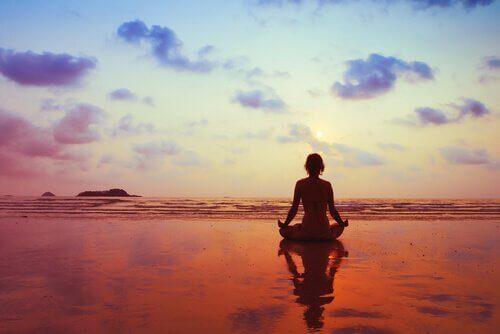 Kvinne som gjør yoga i solnedgangen vil være glad igjen