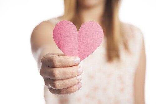 Kvinne holder rosa papirhjerte