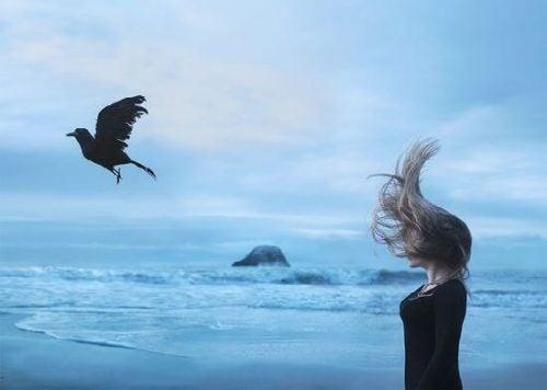 kvinne og fugl ved havet