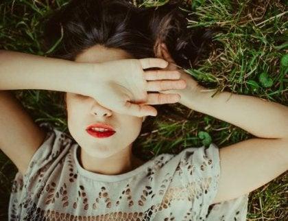 kvinne ligger i gresset med hånden foran øynene