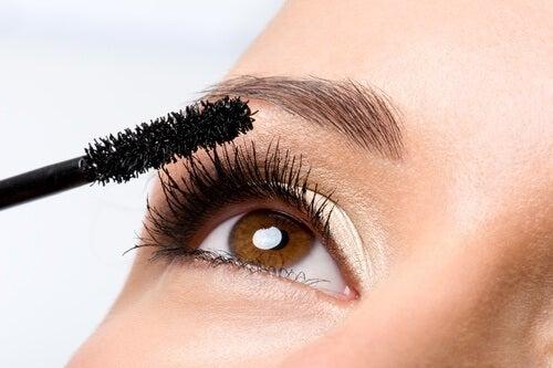 Kvinne med attraktive øyevipper tar på mascara