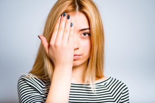 Kvinne med hånden foran øyet
