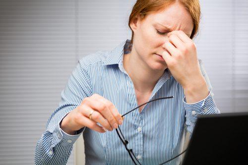 Kvinne på jobb med hodepine