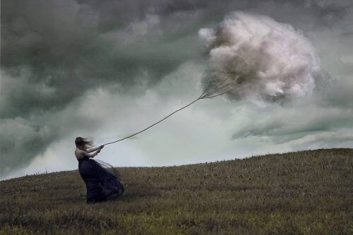 Kvinne holder fast i tau med sky