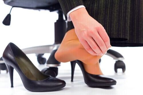 Kvinne har vonde føtter av høyhælte sko