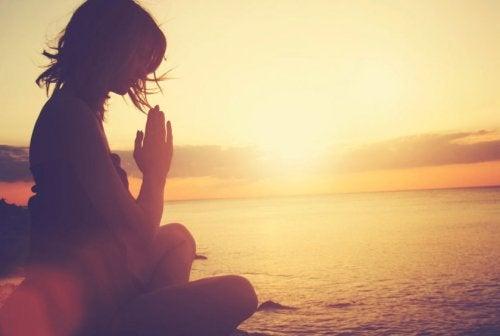 Kvinne mediterer i solnedgang