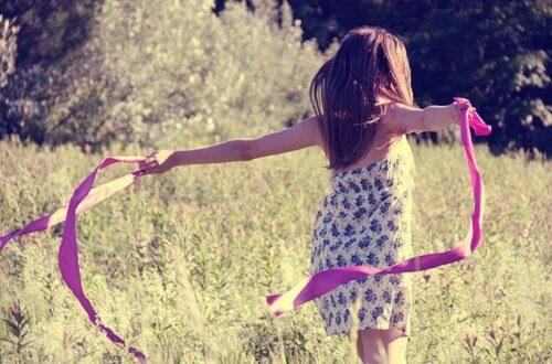 Liten jente løper ute med rosa bånd