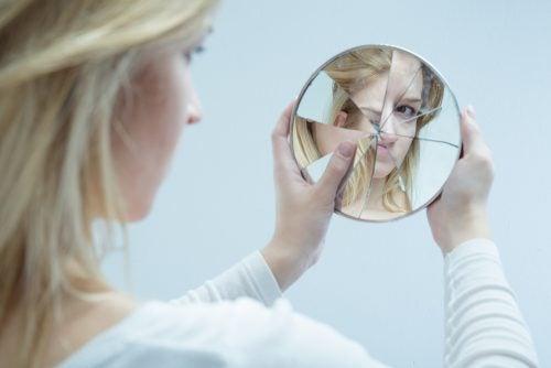 Kvinne ser i ødelagt speil