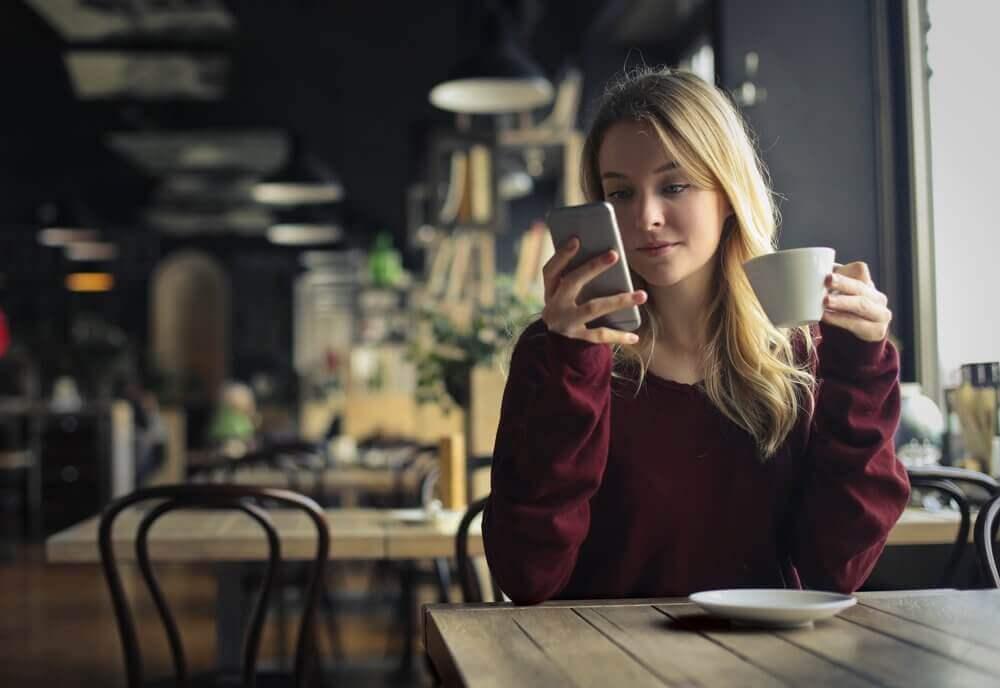 Kvinne på kafé er avhengig av mobiltelefonen sin