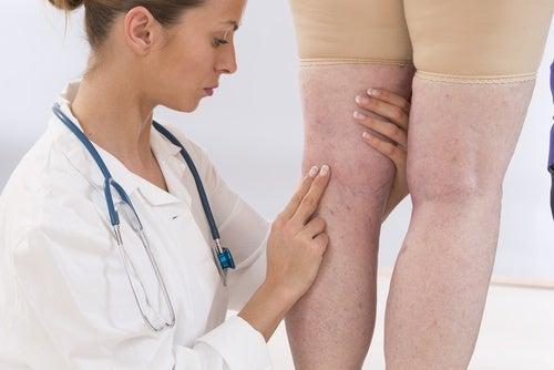 Lege kontrollerer pasients ben