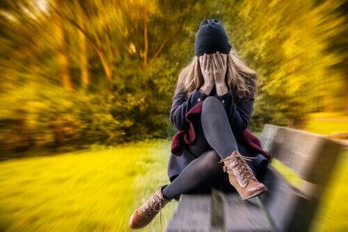 Kvinne med generalisert angstlidelse sitter på en benk i parken