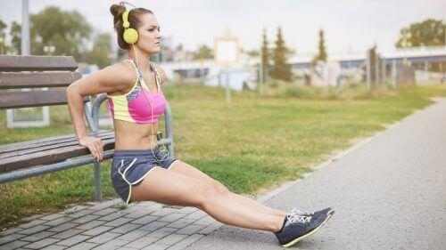 Kvinne trener ute og lytter til musikk