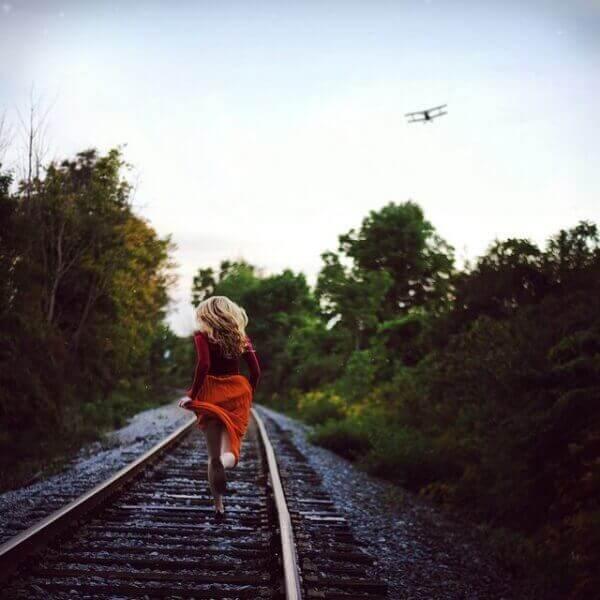 Kvinne løper nedover togskinner