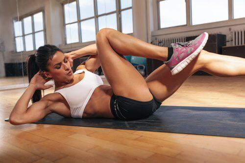 Kvinne gjør øvelser for å trene magemusklene