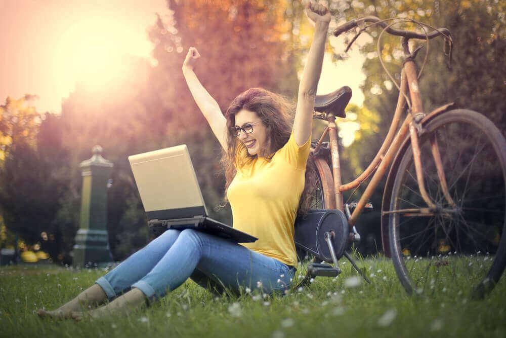 Kvinne med sykkel og PC i parken