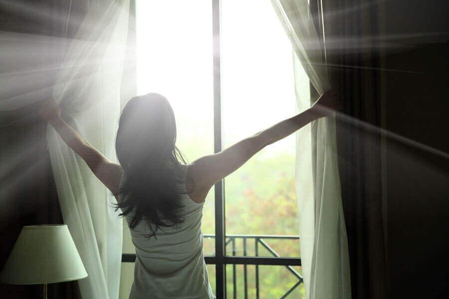 Kvinne åpner gardinene på soverommet