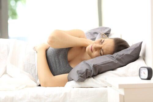 Kvinne i sengen med nakkesmerter