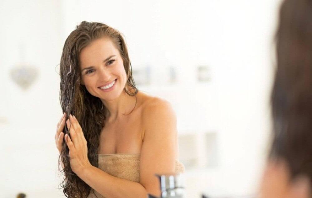 Smilende kvinne påfører eplecidereddik til håret sitt