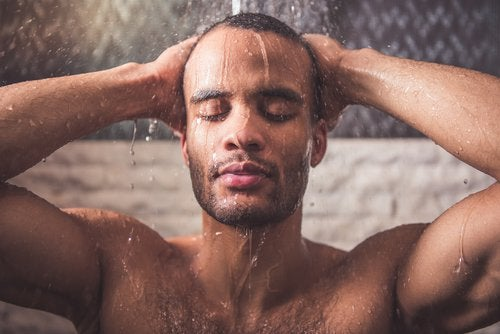 Mann som tar en varm dusj for å redusere nakkesmerter