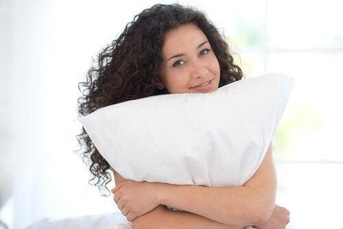 Kvinne med en pute for å redusere nakkesmerter