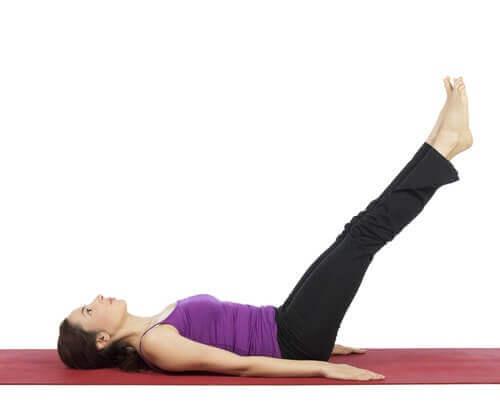 Kvinne strekker seg og gjør yoga for å behandle åreknuter