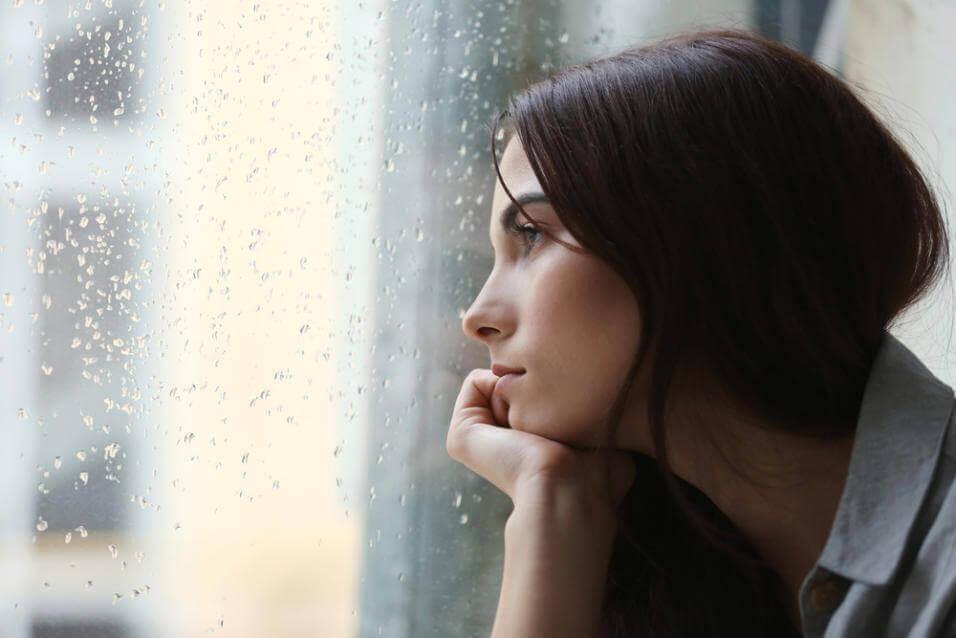 Kvinne med depresjon ser ut av vindu