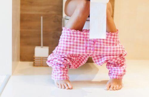 Kvinne med innvollsmark sitter på toalettet