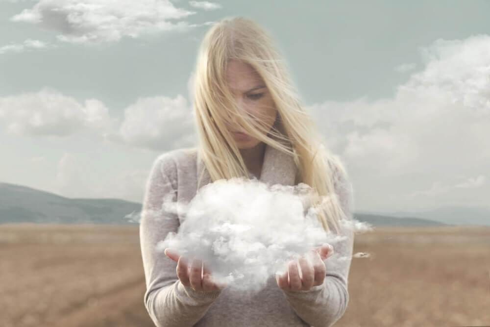 Kvinne ser på skyen i hendene hennes