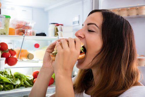 Kvinne spiser usunn mat